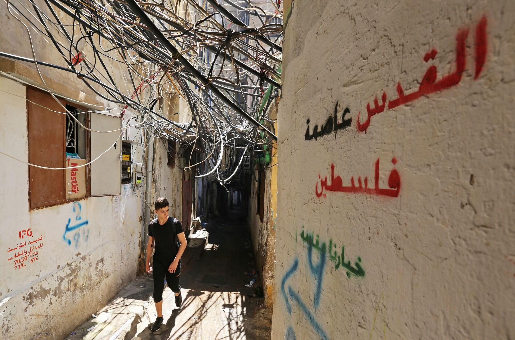 """Un hombre camina cerca de los cables en un campo de refugiados en Beirut, Líbabo. El eslogan en la pared dice """"Jerusalén en la capital de Palestina, nuestra elección es la resistencia""""."""