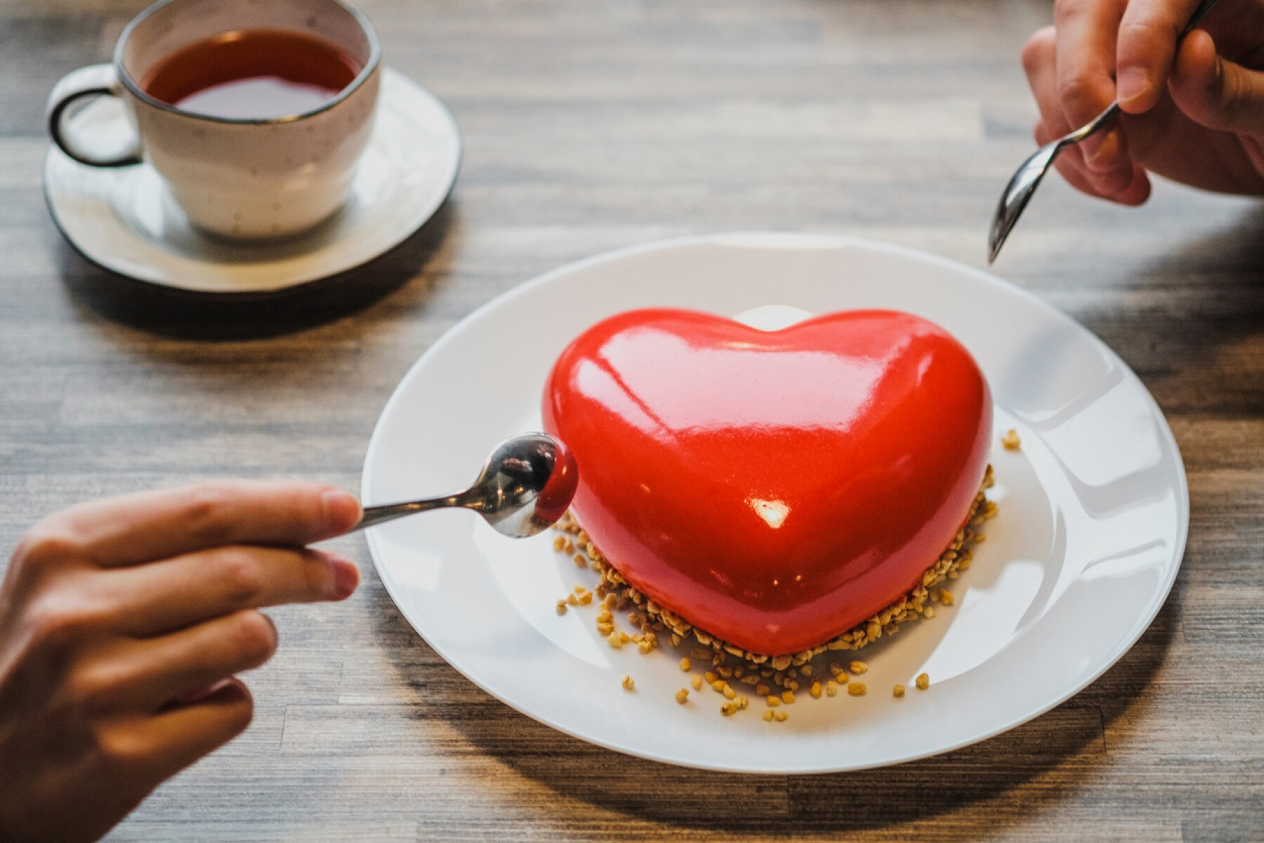 Red cake in the shape of a heart is on the table. Two hands with spoons, male and female, stretch into a pie.