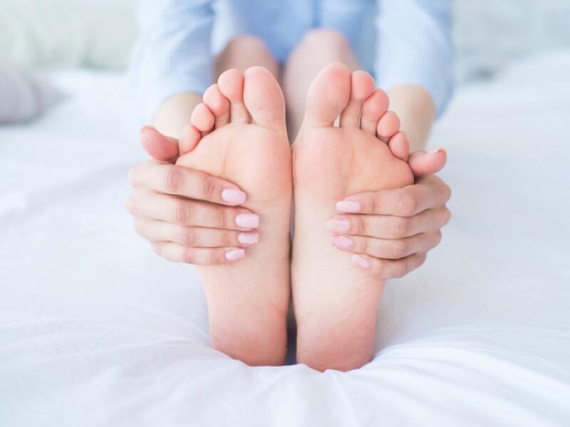 Closeup woman hands doing foot massage