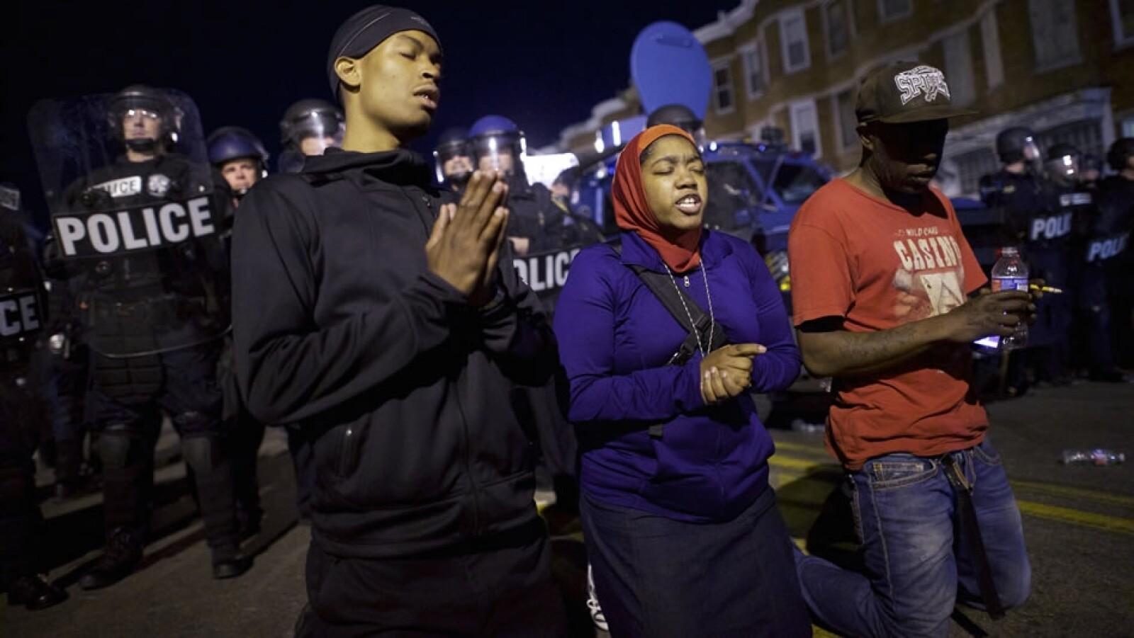 Un grupo de personas reza frente a los oficiales de policía tras resistirse a cumplir con un toque de queda que comenzó este martes