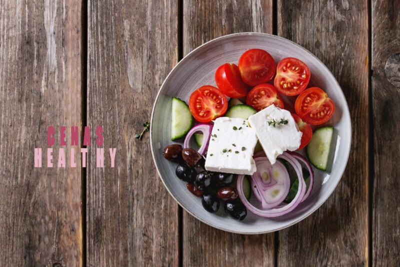 Ingredients for traditional greek salad. Cherry tomatoes, sliced cucumbers, red onion, black olives, feta cheese gray ceramic plate over wooden plank background. Top view with copy space