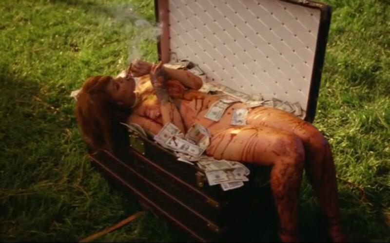 Rihanna aparece desnuda cubierta de sanfre encima de un baúl lleno de dinero.