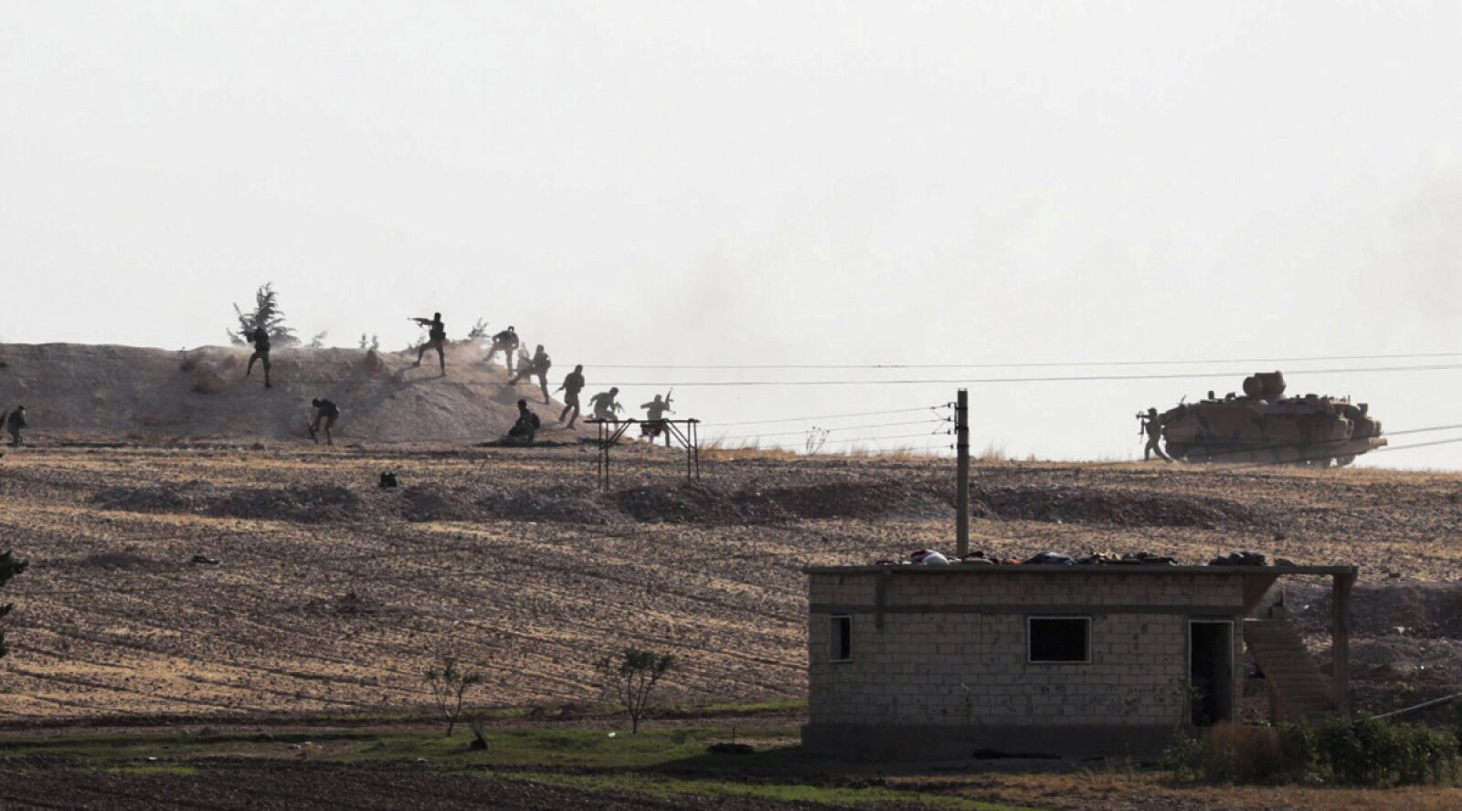 Turkey-backed Syrian rebel fighters are seen in action in the village of Yabisa, near the Turkish-Syrian border