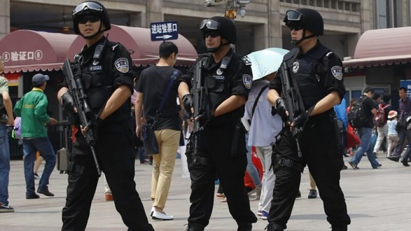 Policías vigilan una estación de tren de Pekín, luego de un atentado el jueves que causó 31 muertos y 94 heridos en la región de Xinjiang
