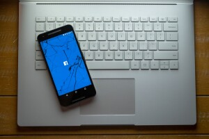 A cracked phone with the Facebook app loading sitting on a laptop