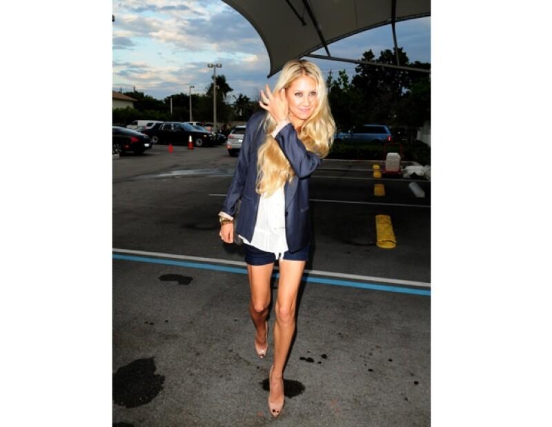 Anna Kournikova usando jean shorts y un blazer azul navy.