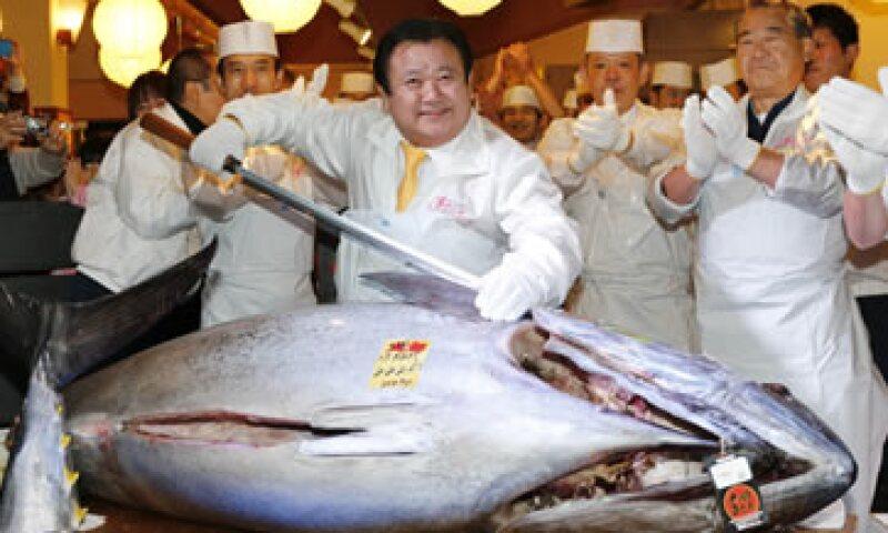 El comprador Kiyoshi Kimura posa junto al ejemplar capturado en la provincia de Aomori. (Foto: AP)