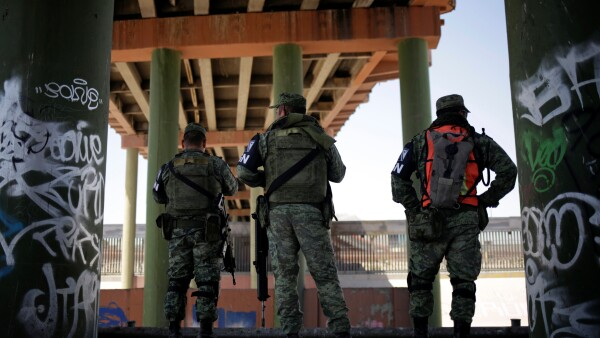 Members of Mexico's National Guard stand under the Paso del Norte International bridge that connects the U.S. and Mexico, as part of an ongoing operation to prevent migrants from crossing illegally into the United States, in Ciudad Juarez