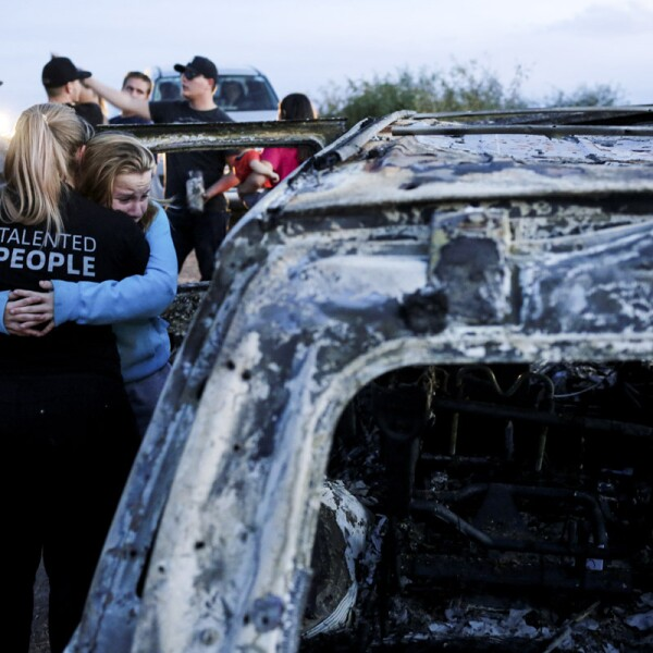 Relatives of slain members of Mexican-American families belonging to Mormon communities react next to the burnt wreckage of a vehicle where some of their relatives died, in Bavispe