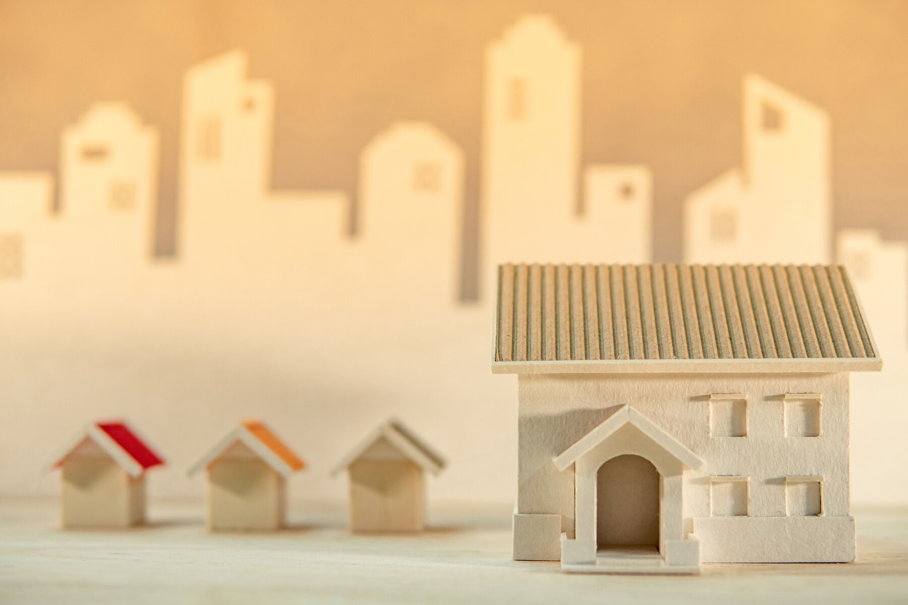 Real estate or property investment. Home design concept. House models on the table with city skyline background. Residential building development