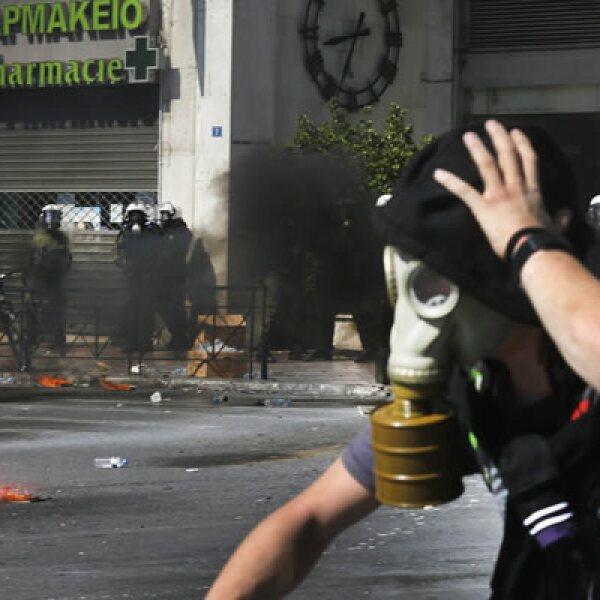 Un manifestante huye de la policía, en la jornada de huelga laboral de 24 horas en el país.