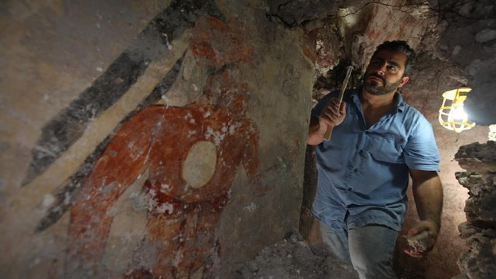 arqueologo William Saturno limpia una pared del habitaculo hallado en xultun
