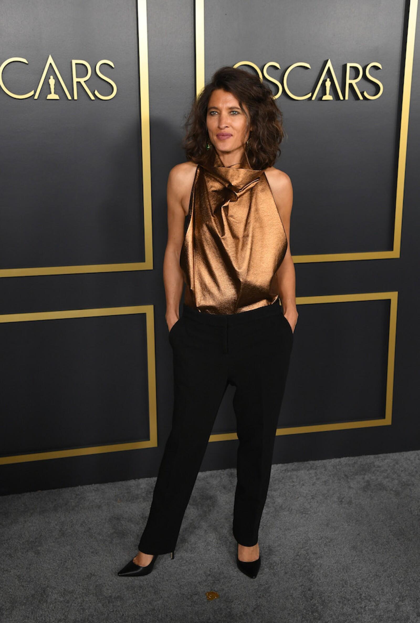 Chelsea Winstanley llevó un top corte halter en color dorado que combinó con unos pantalones sastre negros y pointy shoes