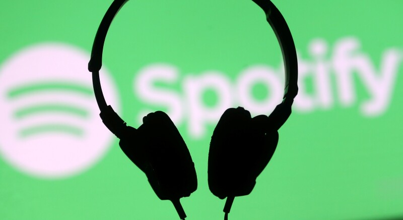 A headset is seen in front of a screen projection of Spotify logo, in this picture illustration