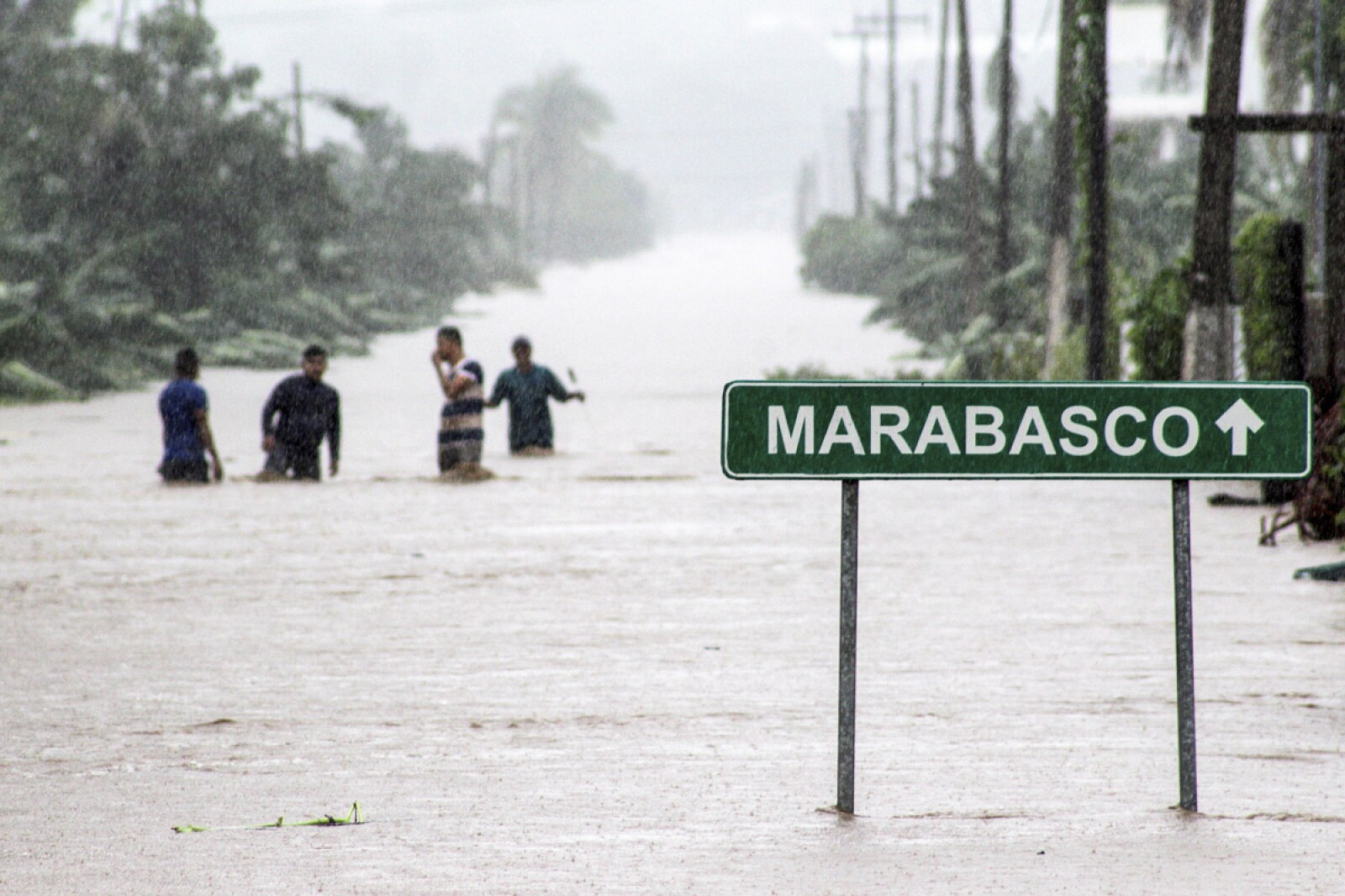 Residents wade through a flooded road during rain storm caused by Tropical Storm Lorena on the outskirts of Manzanillo