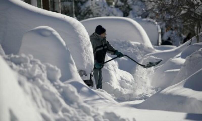 Un residente de Union City retira la nieve de la entrada de su casa, donde quedó sepultado su auto en New Jersey (Foto: Reuters)