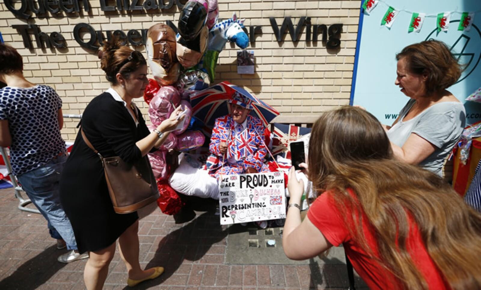 Turistas y medios locales fotografían a un hombre entusiasmado por el nacimiento del nuevo integrante de la familia real.