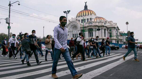 Decenas de personas cruzan hacia la calle de Madero en el Centro Histórico durante el semáforo naranja por Covid-19.
