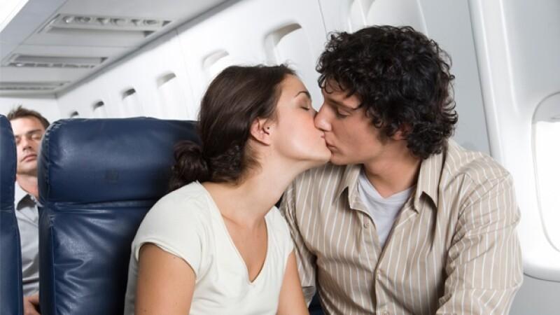 pareja beso avion vuelo