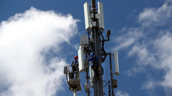 Technicians work on a telecommunication mast near Geneva