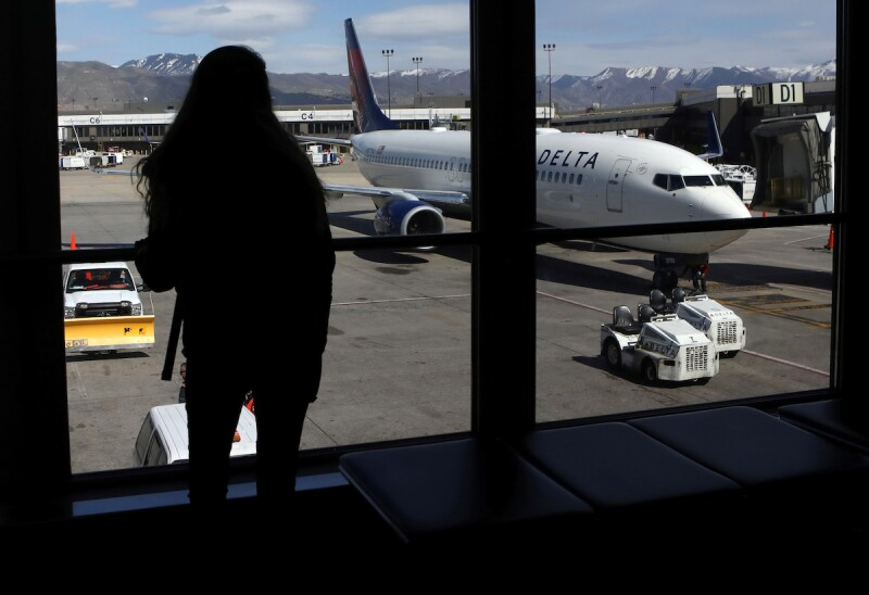 A woman waits for a flight  at Salt Lake City International Airport in Salt Lake City
