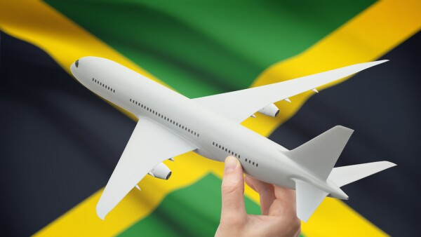 Airplane in hand with flag on background - Jamaica