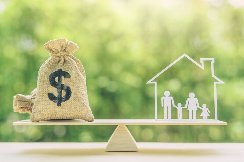 Cost of living, home loan, family finance and child trust fund concept : US dollar bags, family members live inside a house on basic balance scale, depicts the expenditure a family should prepare for