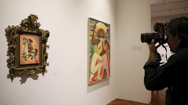 A photographer takes a picture of a painting by artist Fabian Chairez showing Mexican revolutionary hero Emiliano Zapata nude while wearing high heels and riding a horse, at the Fine Arts Palace in Mexico City