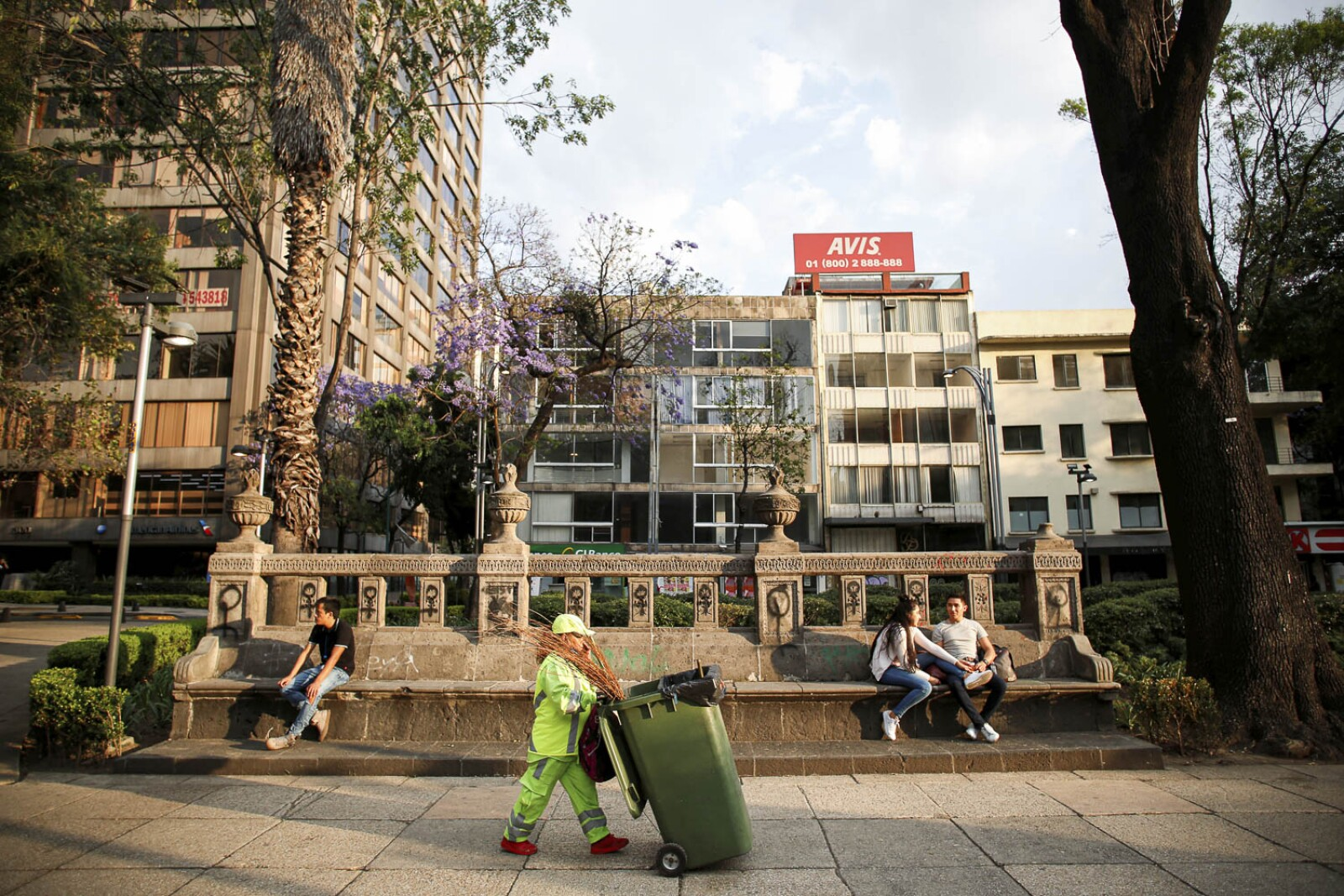 A road sweeper walks past people resting on benches as the coronavirus disease (COVID-19) outbreak continues in Mexico City