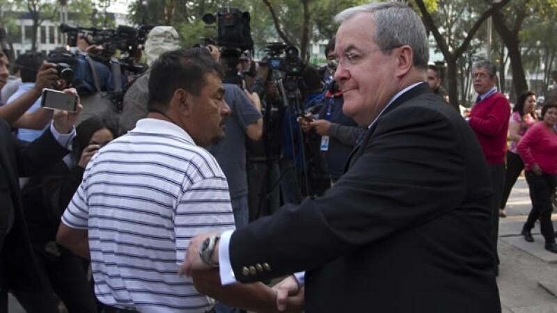 Felipe Flores de la Cruz (izquierda) vocero de los padres de los 43 normalistas desaparecidos en Iguala, saluda a Monte Alejandro Rubido