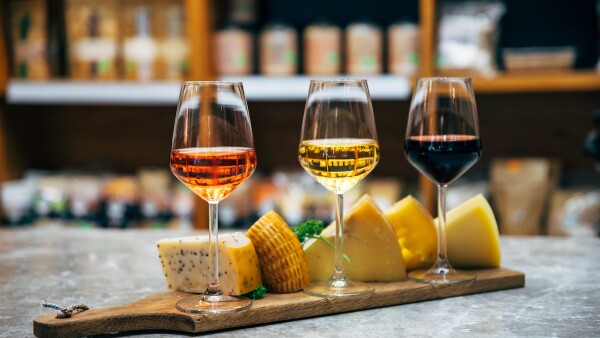 Glasses of Wine and cheese. Assortment or various type of cheese, wine glasses and bottles on the table in restaurant. Red, rose and yellow wine or champagne on the table. Winery concept image