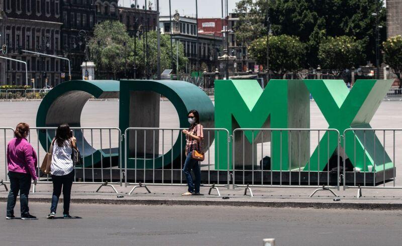 """Turistas se toman una fotografía en las emblemáticas letras """"CDMX"""" ubicadas en la Plancha del Zócalo Capitalino, la cual se encuentra cercada con vallas metálicas para evitar aglomeraciones"""