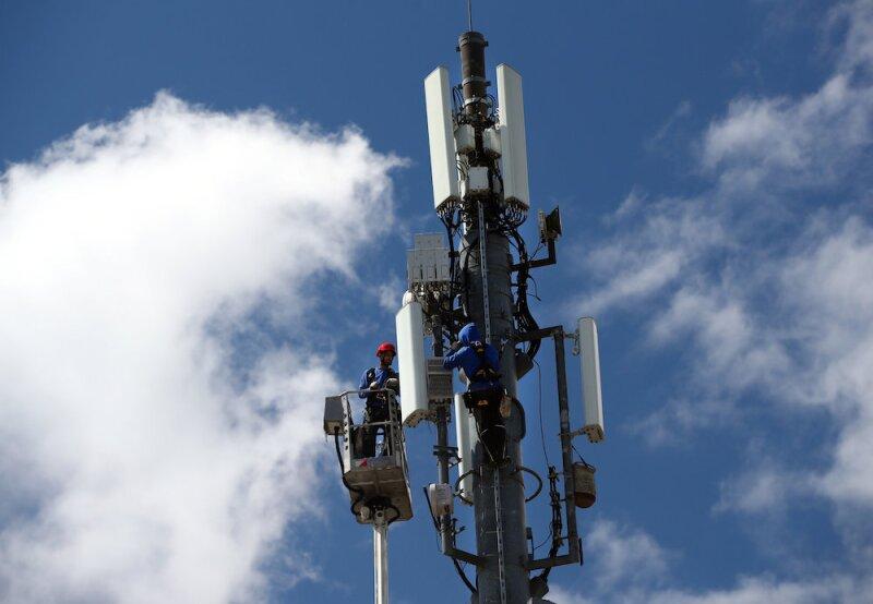 Technicians work on a telecommunication mast near Geneva