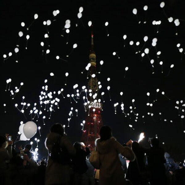 La Torre de Tokio se ilumina para recibir el 2013, mientras la gente suelta globos.