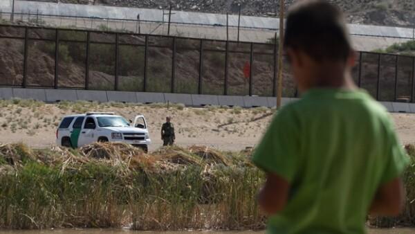 Un menor observa a un agente de la Patrulla Fronteriza en la línea divisoria entre México y Estados Unidos