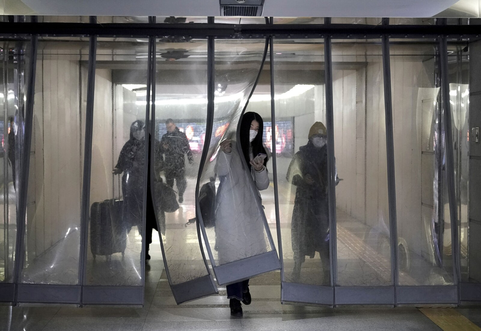 People wearing masks walk through an underground passage to the subway in Beijing