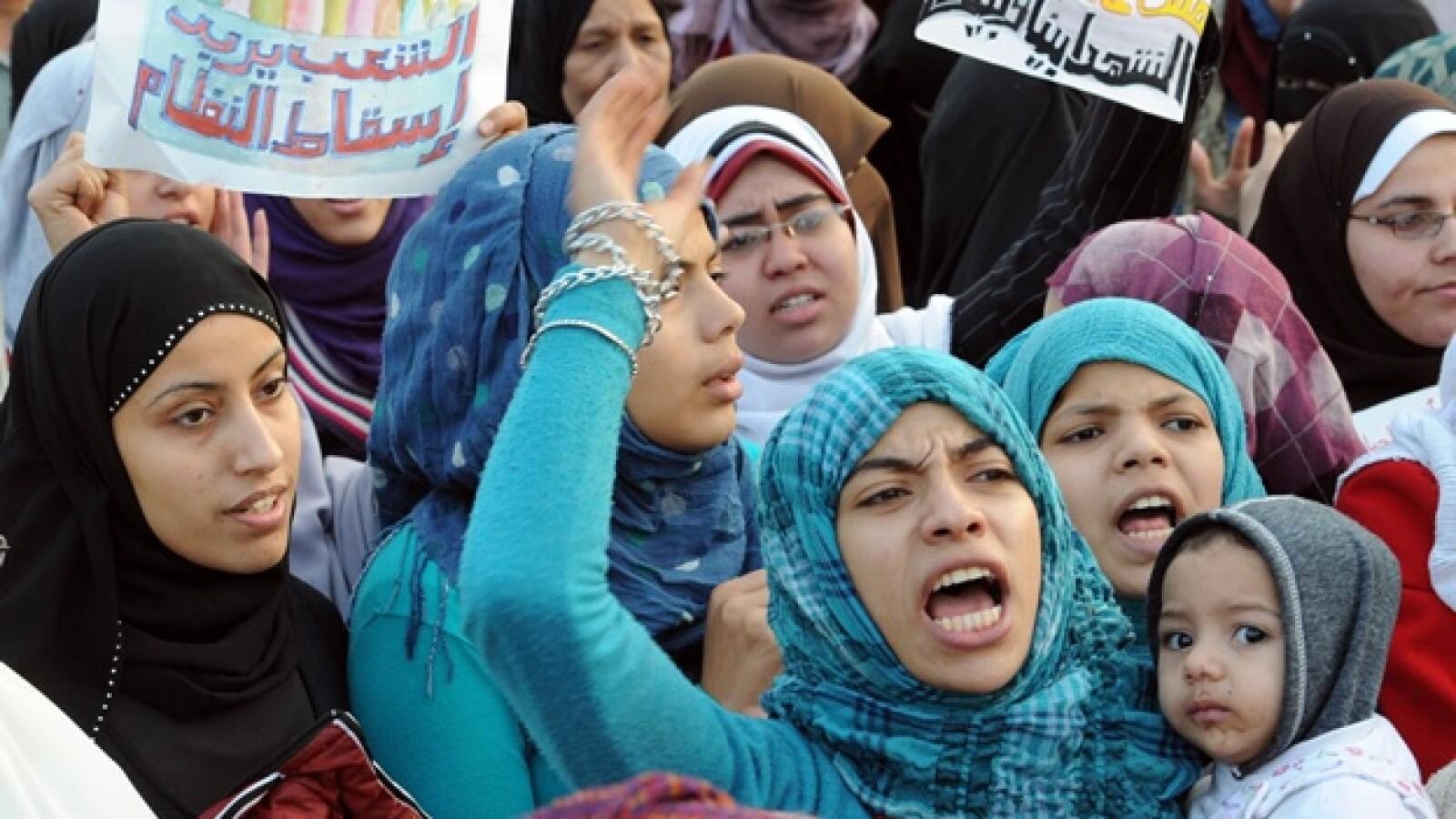 Una adolescente sostiene un cartel contra Mubarak