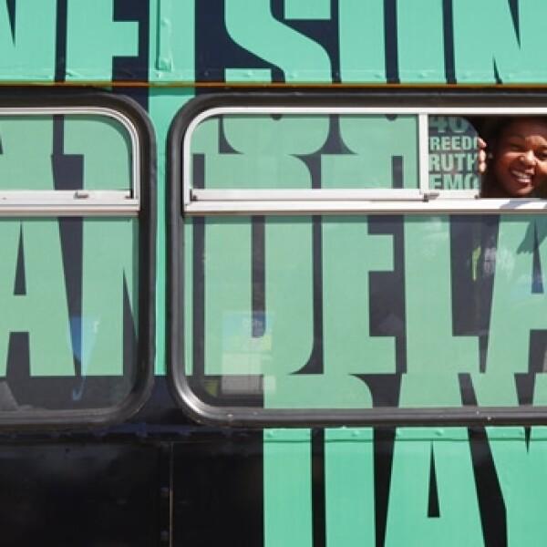 una mujer saluda desde un autobus en soweto, johannesburgo