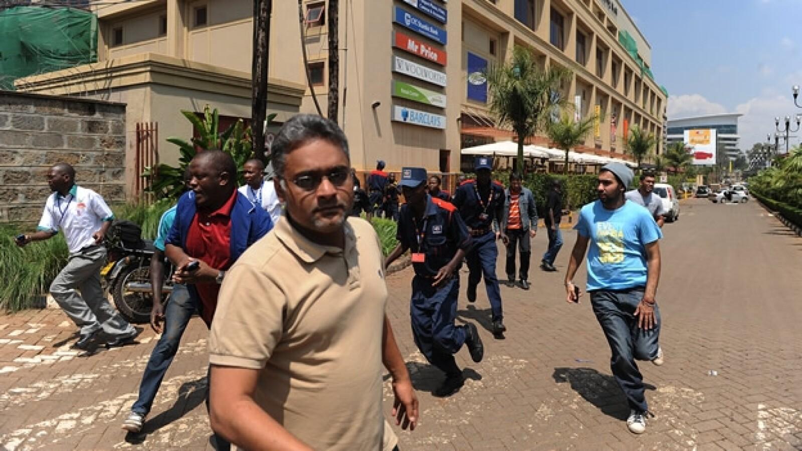 hombres corren lejos del centro comercial