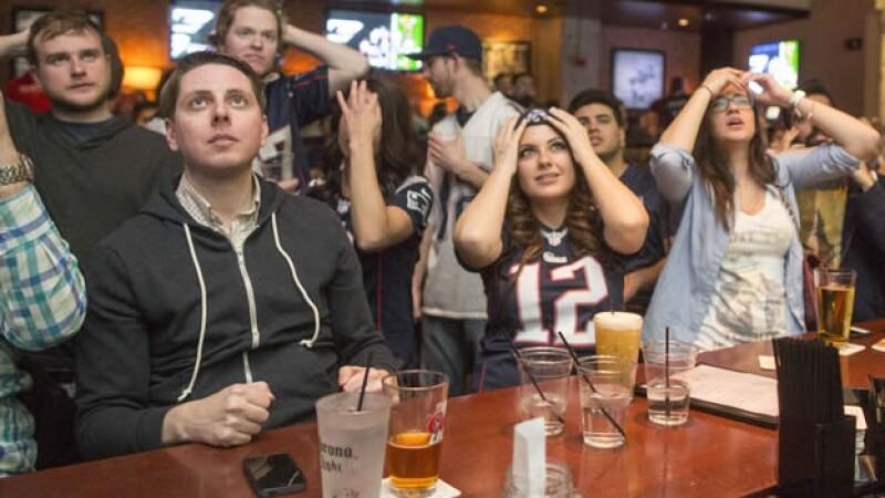 Los fanáticos de los Patriotas reaccionan ante una jugada de su equipo en un bar de Boston el domingo