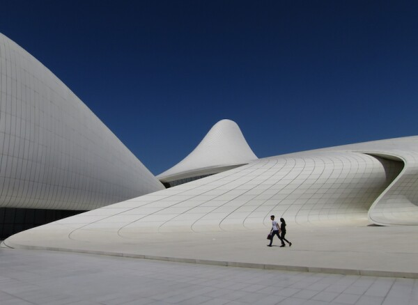 Two people walk across the plaza at the Zaha Hadid designed Heydar Aliyev Center in Baku, Azerbaijan