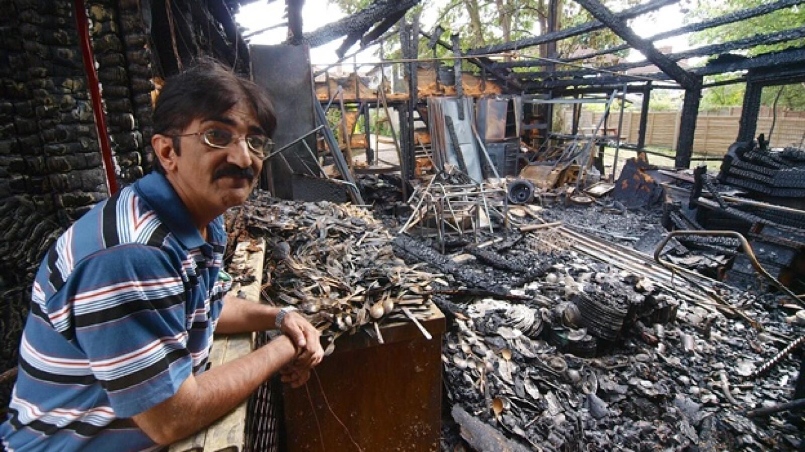 Azim Mohamed observa los restos de su negocio quemado