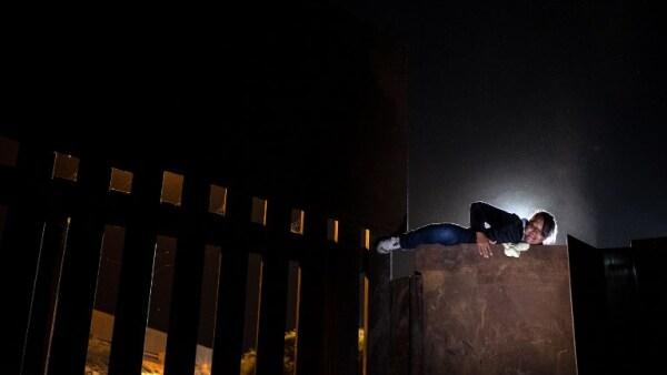 Familias de migrantes intentan escalar el muro fronterizo