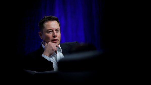 FILE PHOTO: Tesla Chief Executive Elon Musk stands on the podium as he attends a forum on startups in Hong Kong