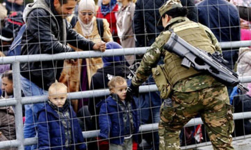 Un soldado de Eslovenia platica con migrantes en la frontera con Austria. (Foto: Reuters)