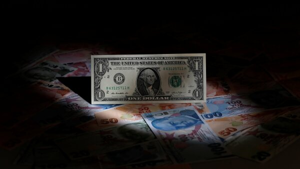 A U.S. dollar banknote is seen on top of Turkish lira banknotes in this picture illustration in Istanbul