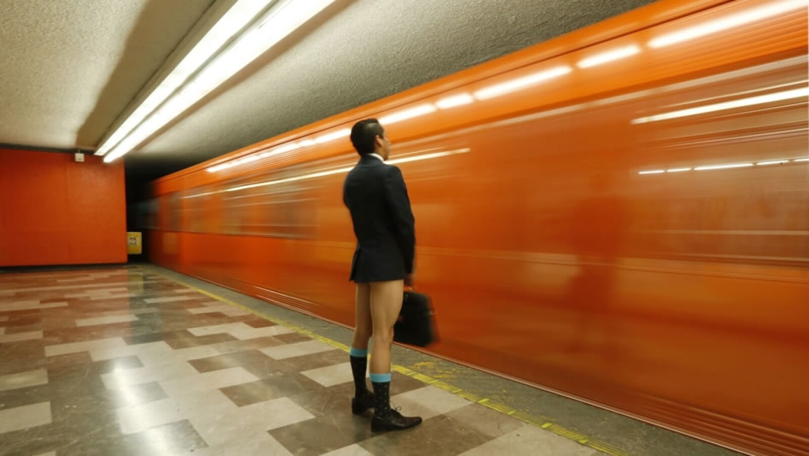 Sin pantalones pero con saco y zapatos de vestir esperando el Metro