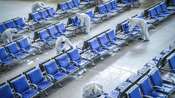 Los trabajadores en trajes de protección desinfectan una sala de espera en la estación de tren de Wuhan que se había cerrado debido al nuevo brote del coronavirus, en Wuhan.