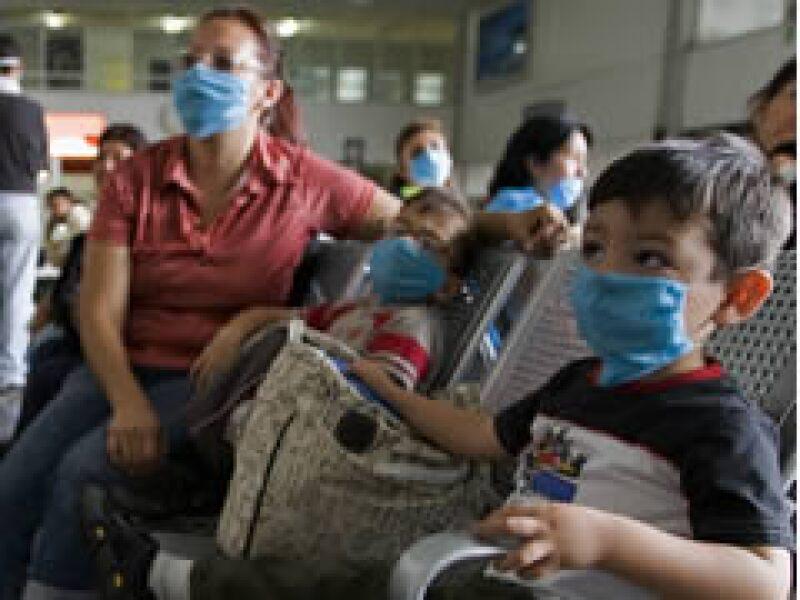 Madre e hijos se protegen del virus de la influenza porcina con tapa bocas. (Foto: Reuters)