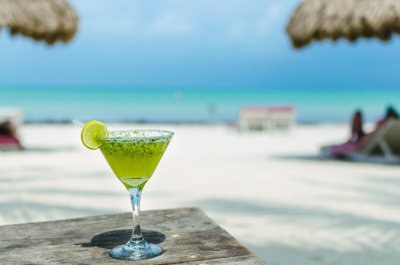 Fresh Margarita cocktail on a table at tropical sandy beach